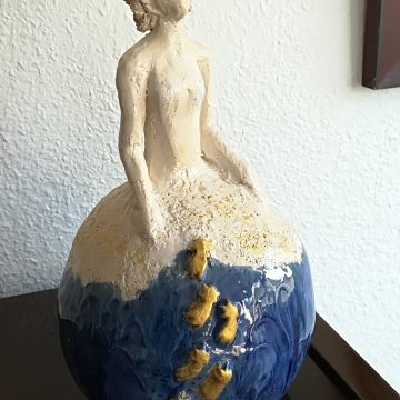 sculpture d'une femme assise sur la terre en confiance